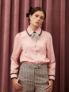 Classic shirt in a soft touch fabric. Detailed with a contrast pleated trim and gem buttons. A removable embellished velvet bow finishes the look.