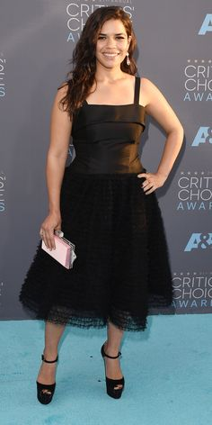 Critic's Choice Awards 2016: AMERICA FERRERA wears a black dress with a structured top and gathered tulle skirt, plus matching Brian Atwood platforms, then brings in pale pink elements via her clutch and Irene Neuwirth jewelry.