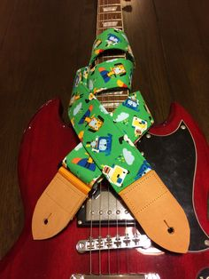 Cool guitar strap -- cute cartoon dogs -- bright and colourful on a green background by MyMumDrivesaUFO on Etsy