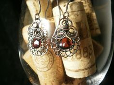 Garnet drop surrounded by swirls of copper hang on copper earwires. ~ Designed by The Feathered Mane