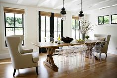 Modern rustic dining room featuring a large wood table, linen covered wing chairs, Louis Ghost chairs, and vintage industrial pendant lights - Home Decor & Decorating ideas - Beautiful Rooms With a Contemporary Farmhouse Style   Apartment Therapy