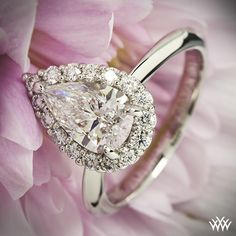 This beautiful Custom Solitaire Engagement Ring is set in platinum and has a clean knife edge shank that leads to a pear shaped halo shining with 0.45ctw A CUT ABOVE® Hearts and Arrows Diamond Melee that surround a 1.29ct internally flawless pear cut diamond.