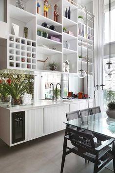 Decoração de apartamento. Na sala de jantar, jardim vertical, luz natural, parede de tijolinhos, mesa de jantar retangular de vidro, plantas, flores e cadeira preta. #decoracao #decor #design #details