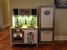 Ikea Duktig mini-kitchen makeover.  Added paint, tile backsplash, oven knobs, and lighting.  Our son LOVES it!!!   Billy bookcase used to make refrigerator, which is great for extra play food storage.