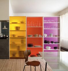 These colorful shelves act as room dividers and storage pieces. Three IKEA Billy Bookcases were customized by replacing the standard backs with acrylic plexiglass plates cut to size and screwed into the backs of the cases.
