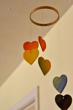 Rainbow heart mobile - embroidery hoop, floss, wooden hearts from AC Moore... inspirtation: parents can buy raw materials and customize by painting, etc? Or have options of shapes, etc.