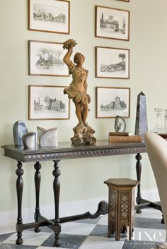1950s etchings depicting Roman scenes frame a statue in this vignette | LuxeSource | Luxe Magazine - The Luxury Home Redefined