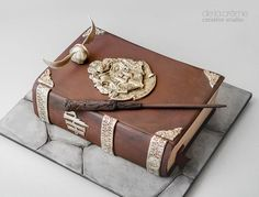 Harry Potter inspired cake designed by De la Creme Creative Studio - A Golden Snitch, Harry Potter's wand and a Hogwarts Crest all sculpted by hand!