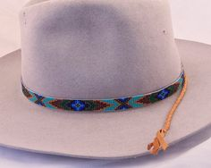 This Beaded Hatband of Neutral Colors in Dark Gold, Browns, Black, Emerald Green and Blues on a Turquoise Background in a Geometric Design is a stunning piece on a Western Felt or Panama Straw Hat. Hand made by the Artist, this design is inspired by Native American Beadwork. The beads used are Japanese Delica Glass Seed Beads. These beads I love to work with on loom work pieces because of their symmetrical size and tubular shape. They create a beautiful weave. The beaded strip is 22 long by…