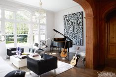 If you're scanning about in search of the formal dining room, don't bother—there was one, but this family didn't want it. They all play instruments, so Smith turned it into a music room, which holds their Steinway piano, a chic graffiti painting by the artist Retna, and big, square midcentury chairs upholstered in black pony skin. Vintage Milo Baughman chairs in Caldelle Leather cowhide. Grand piano, 76 Steinway. Throw on sofa, Hermès. Art, Retna.
