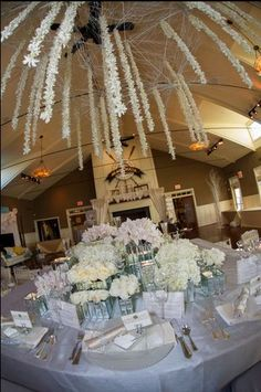 http://intrigue-designs.com/ Suspended centerpiece created out of thousands of orchids strung into white garlands on giant branch snowflakes over a glamorous table composed of blush cymbidium orchids, sweetpea, roses, lisianthus and hydrangea designed in mirrored vases vintage rentals www.2handsstudios.com,  photography hamiltonphotography.net, planning www.annapolisweddingplanner.com, paper www.thepapertrousseau.com