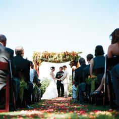 The couple exchanged vows under a frame draped with roses, orchids and calla lilies in summer citrus colors