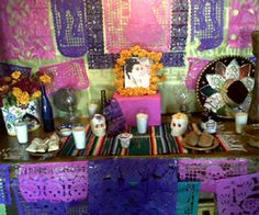 An altar de muertos dedicated to the late singer Lola Beltran, whose CD centers the altar. Plates hold tamales and bread; a bottle of liquor...