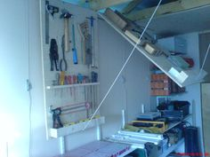 CEILING TOOL STORAGE, USING HINGED PANELS AND PULLY TO SECURE TOOLS OUT OF THE WAY IN CEILING.