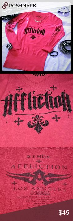 Affliction ~ V-Neck Sweater Tunic /Dress Very cool Affliction sweater dress in an awesome red/coral w black graphics, adorned w black rhinestones, on front as well as down both arms. ALL stones intact! This is labeled a size large, but fits medium great as well. For reference, I'm 5'9 and normally a med. (sometimes med/lg) and it's a nice body forming fit that hits mid-thigh if worn as a dress. Overall excellent condition, however there is a very small split in the seam in one armpit. and…