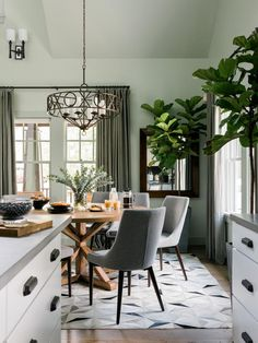 Midcentury-style chairs mix with the rustic-look table and traditional lighting and window treatments, proving there's no reason to stick with just one style to get a stylish look.