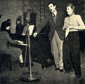 Anne Ziegler singing with Webster Booth, her husband and partner (1902-1984), during broadcasting from a basement in 1940. World War II. Duet.  British singer, 22 June 1910 - 13 October 2003.
