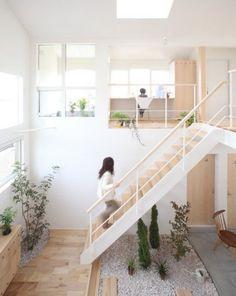 decoration zen a l interieur d une maison moderne, un carré zen de gravier et plantes bas, deux étages, accents en bois, idée jardin sous pente