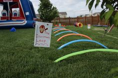 Superhero Training Center - Superhero Obstacle Course - The Ironman Leap.  Pool Noodles cut length wise.  $1 each from The Dollar Store.  Attached to the ground with garden staples from Walmart. You get like a dozen for $1.98.