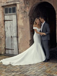 Rebecca Ingram Josie Huron Mikado creates this exquisite fit-and-flare wedding dress featuring a sweetheart neckline with off-the-shoulder sleeves and covered buttons trailing down the train. Finished with covered buttons over zipper closure. Fit And Flare Wedding Dress, Sweetheart Wedding Dress, Classic Wedding Dress, Dream Wedding Dresses, Satin Mermaid Wedding Dress, Simple Elegant Wedding Dress, Wedding Dress Train, Off Shoulder Wedding Dress Simple, Fitted Wedding Dresses