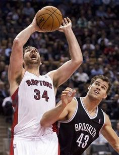Toronto Raptors forward Aaron Gray (34) tries to drive past Brooklyn Nets forward Kris Humphries (43) during the first half of an NBA basketball game in Toronto, Wednesday, Dec. 12, 2012. (AP Photo/The Canadian Press, Nathan Denette)