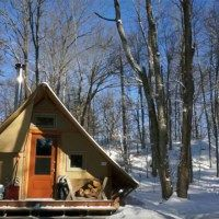 In this video, you'll get a tour of a prospector-style, 4-season tent that is completely off-grid. The tent is built with two layers of weather-proof canvas stretched over a wooden frame and is equipped with a double combustion wood stove for heat, a solar panel to power 1 LED light, and a propane fridge to