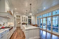 White kitchen that opens up to screened in porch