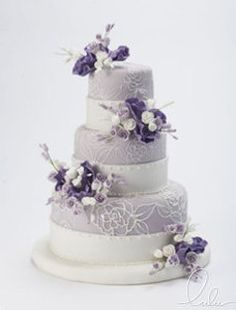 Handcrafted eatable flowers enhancing a white flower embossed lavender fondant.