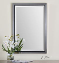 "Uttermost Rashida Chrome Mirror Polished, chrome plated metal frame accented with a matte black inner lip. Mirror has a generous 1 1/4"" bevel. May be hung horizontal or vertical. Designer: 	Grace Feyock Dimensions: 	22 W X 32 H X 2 D (in)"