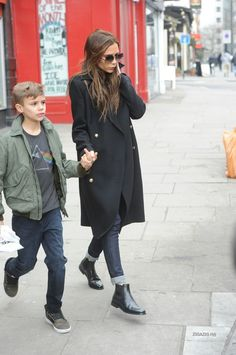 Victoria Beckham in a long wool coat, rolled up jeans, and chelsea boots.