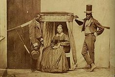 a white woman and her two slaves. she shows her fortune by making her slaves look nice.Woman and her slaves in São Paulo, c. 1860
