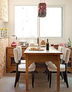 A copa, considerada a sala de refeições do dia a dia, ganhou decoração rústica. A parede de tijolos completa o clima e quebra a frieza do espaço