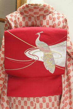 こっくりとした綺麗な赤色の地に、凛と浮かぶオーロラ色の孔雀が美しい開名古屋帯です。
