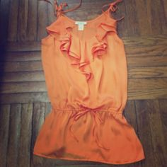 Arden B tunic Orange Arden B. tunic worn a few times. Ruffle details cinched at waist. The string does not make the top tighter at the waist. Top does tie at arms so you can adjust how high or low you want the top to be. Arden B Tops Tunics