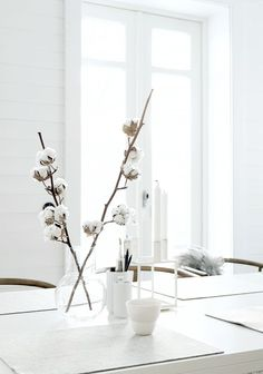 Modern simplicity. White cotton blooms and nondescript vases brighten up a classic all-white decor scheme.