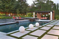 Geometric pool and pergola with dome lanterns, stone pavers in pattern on grass lawn. Creative Environments, Alamo, CA http://www.luxurypools.com/swimmingpoolbuilder/Creative-Environments?fid=67  Photography by Vern Nelson