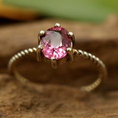 Oval faceted pink spinal ring in prongs setting with sterling silver twist band