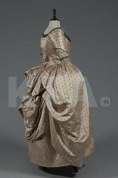 A brocaded silk open robe 'a la polonaise', circa 1785-90, of figured oyster silk woven with small floral sprigs, edged in peacock-green satin, the closed-front bodice with pointed low waist, single bone to fitted centre-back; together with a pale quilted pale pink silk petticoat adorned with quatrefoils and scrolls, (2)