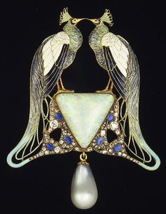 René Lalique pendant via The Metropolitan Museum of Art. Features two symmetrically facing peacocks perched on a mother of pearl design with a pearl drop hanging from the bottom.