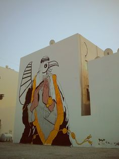 Street art seen in Adliya, Bahrain. A big ol' mural on the wall of the two storey building.