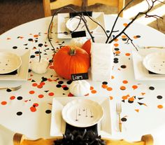 You won't have to buy a ton of supplies to execute this simple table idea. All you need are a few small and big pumpkins for the centerpiece, plus place card holders, black and orange cardstock for the confetti, place cards, black napkins, simple white plates, and striped twine for the cutlery.