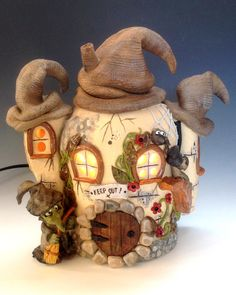 Witches Cottage Pottery Lamp This little witch is cleaning her cottage, unfortunately the spiders and insects living amongst the foliage make it difficult! Along with her black cat she is looking for a piece of land to move her home to, maybe you have one available?