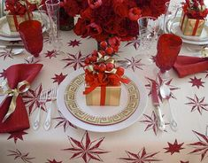 """MICHAEL DEVINE  Fabric designer and retailer,   """"I think of myself as a modern traditionalist. My favorite color choice for a festive table is always red. No other color packs the punch that red does. I love single-color arrangements of roses, tulips, and carnations, so I did four of them for the centerpiece around an antique hurricane. The tablecloth is my very cheerful Celeste pattern."""