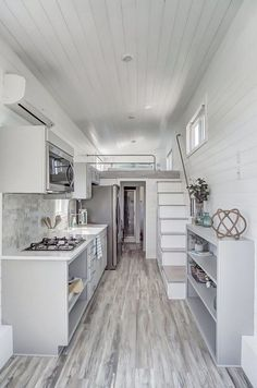 A white farmhouse sink, four burner cooktop, over the range microwave/venting hood, and full size refrigerator make the kitchen as functional as it is beautiful. house design Fox by Modern Tiny Living - Tiny Living Tiny House Loft, Best Tiny House, Modern Tiny House, Tiny House Living, Tiny House Plans, Tiny House On Wheels, Living Room, Tiny House Luxury, Tiny Loft
