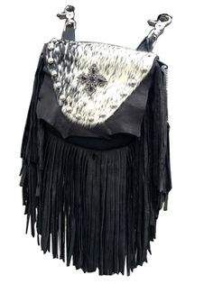 """GALWAY MARTY - super soft, made of black deerskin with a 7"""" black deerskin fringe. The flap features an absolutely stunning pattern of black and white hair-on-hide cow. The centerpiece is a bold silver and black Celtic cross. Etched silver metal studs highlight the flap. Wear bag clipped to belt loops for hands-free carrying of your essentials. Interior includes a leather strap. Add the strap when you want a completely different look."""