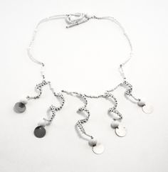 Fun curly necklace has beaded white spirals with feather light silver metal discs on each end that sparkle and look great!