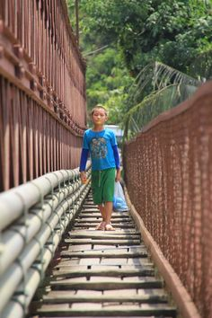 Little boy eating mango on the bridge - Luang Prabang