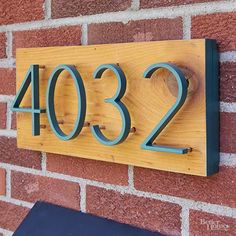 Make a modern house plaque: Trim a 1×8 cedar board to the desired width. Using a brad nailer, attach 1×1-inch square dowels around the back perimeter of the board. Seal the front; let dry. Protect the front with painters tape, and paint the edges. Using the provided templates, drill holes for the metal house numbers (we painted ours teal). Apply clear silicone in each hole, and insert the numbers. When dry, mount a ledger board to the house, and install the plaque by driving screws through…