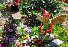 Our sly little fairy elf waits for mail in our miniature fairy garden.