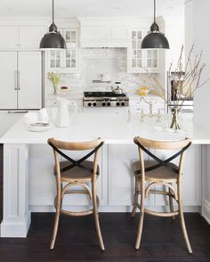On dark hardwood floors, two french cafe bar stools with leather x-back straps sit in front of a gorgeous white peninsula topped with white quartz countertops and fitted with a deck mount vintage faucet accenting an undermout kitchen sink illuminated by two industrial black pendants.